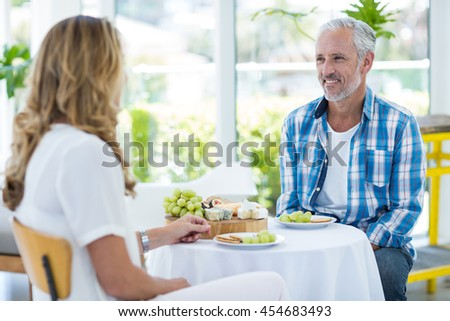Happy mature couple sitting in restaurant - stock photo