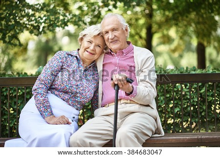 Happy mature couple sitting on bench in the park - stock photo