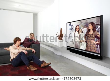 happy mature couple sitting on couch and watching television together - stock photo