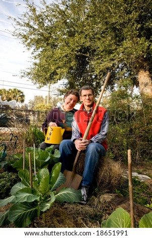 Happy mature couple sitting on hay bales in their collards garden. - stock photo
