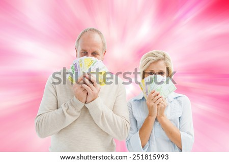 Happy mature couple smiling at camera showing money against digitally generated girly heart design - stock photo