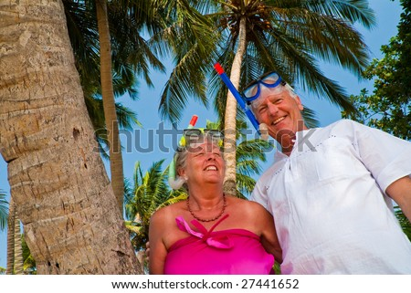 Happy mature couple smiling in the shade of palm trees on the beach. They are wearing snorkeling gear and in the background is the blue sky with palms. - stock photo