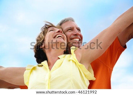 Happy mature couple standing with arms outstretched. - stock photo
