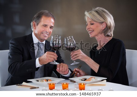 Happy Mature Couple Toasting Wine In A Elegant Restaurant - stock photo