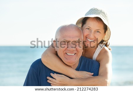 Happy mature couple together at sea beach - stock photo