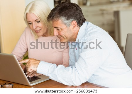 Happy mature couple using laptop at home in the kitchen - stock photo