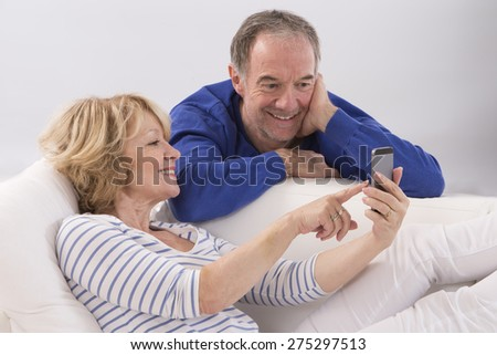 Happy mature couple using smart-phone together at home in living room - stock photo