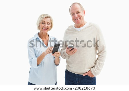 Happy mature couple using their smartphones on white background - stock photo