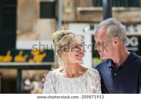 Happy mature couple walking arm in arm along an urban street smiling affectionately into each others eyes - stock photo
