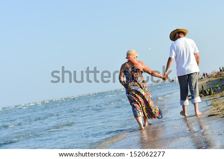 Happy mature couple walking & having fun outdoors at seashore on sandy beach and embracing on holiday - stock photo