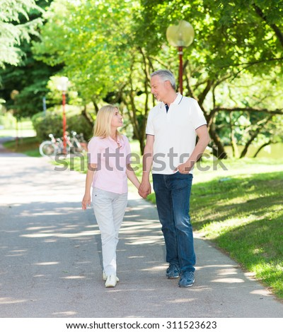 Happy mature couple walking in a park while holding hands - stock photo