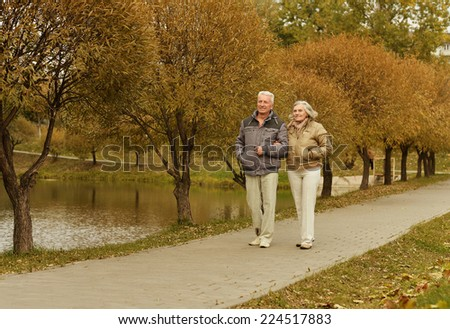 Happy mature couple walking in  autumn park - stock photo