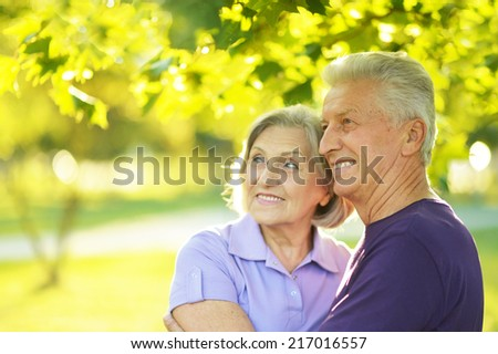 Happy mature couple walking in the park in the afternoon - stock photo