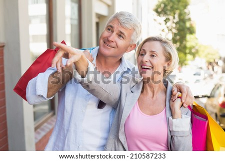 Happy mature couple walking with their shopping purchases on a sunny day - stock photo