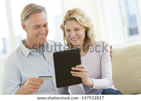 Happy mature couple with credit card and digital tablet shopping online at home - stock photo