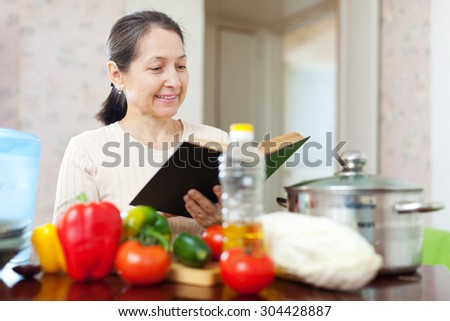 Happy mature housewife reads cookbook for recipe at home - stock photo