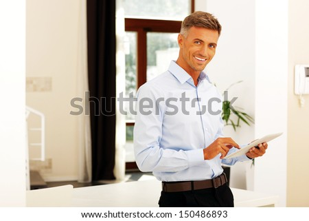 Happy mature man using tablet - stock photo