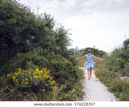 Happy mature senior woman looking fit as she walks on sandy path through beach sand dunes with flowering island plants and vegetation. - stock photo