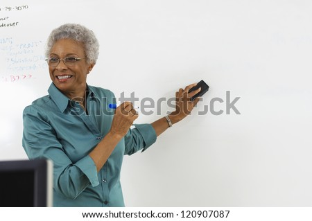Happy mature teacher explaining a lesson in classroom - stock photo