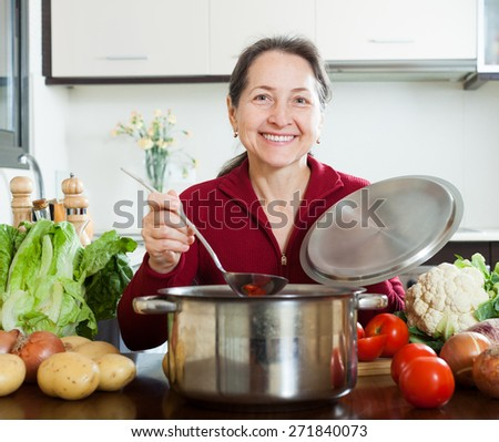 Happy mature woman cooking lent diet soup in  kitchen - stock photo