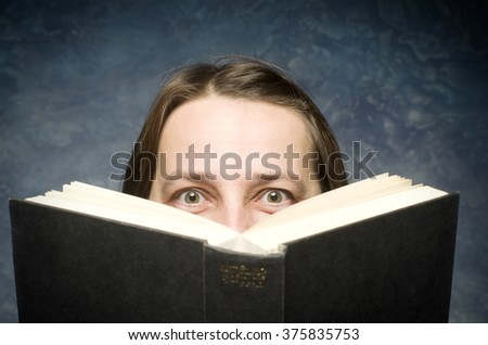 Happy mature woman hiding behind book on blue background. - stock photo