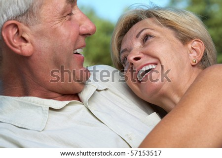 Happy mature woman leaning against a man - stock photo
