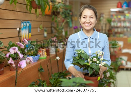 Happy mature woman looks Clerodendrum plant at flower store - stock photo
