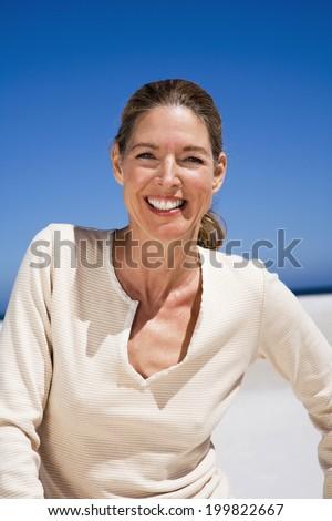 Happy mature woman on beach smiling portrait - stock photo