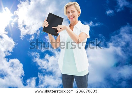 Happy mature woman pointing to tablet pc against bright blue sky with clouds - stock photo
