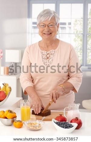 Happy mature woman preparing healthy breakfast, slicing brown bread, looking at camera. - stock photo