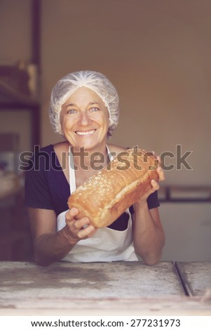 Happy mature woman selling bread - stock photo