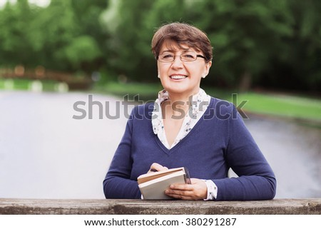 Happy mature woman taking notes - stock photo