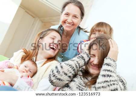 Happy mature woman with her daughters and granddaughters in home - stock photo
