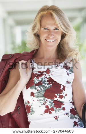 Happy mature woman with jacket smiling outdoors - stock photo
