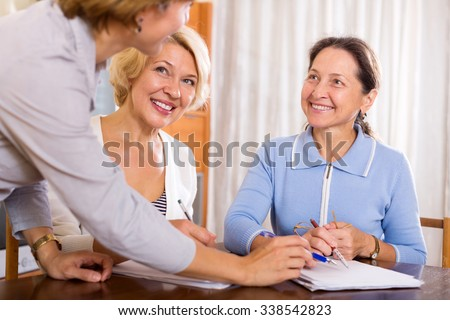 Happy mature women consulting at insurance agent office. Focus on the left woman - stock photo