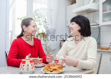 Happy mature women talking over coffee in kitchen. - stock photo