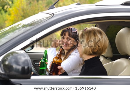 Happy matured women drinking alcohol inside the car - stock photo