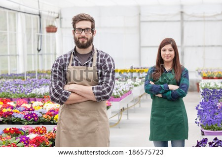 Happy  men and female florist working indoors with her young coworker  - stock photo