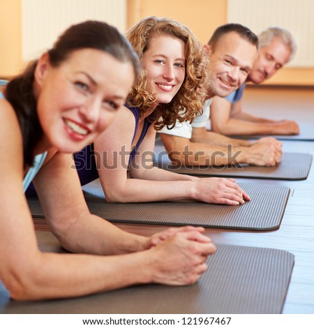 Happy men and woman laying smiling on gym mats in a fitness center - stock photo