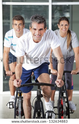 Happy men and woman on bikes in health club - stock photo