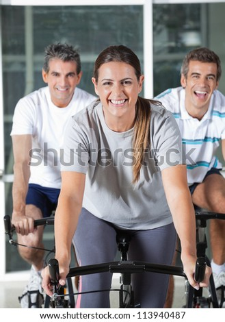 Happy men and woman on exercise bikes in health club - stock photo