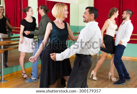 Happy men and women enjoying active dance - stock photo