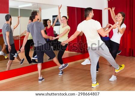 Happy men and women enjoying the active dance in the dance studio  - stock photo