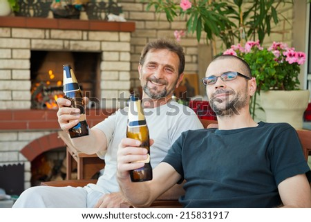 happy men are sitting in front of fireplace with beer bottles cheering and smiling - stock photo