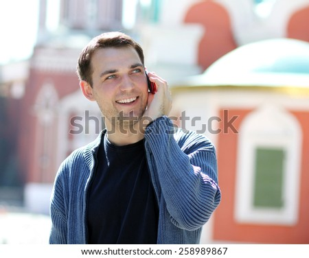 happy men calling by phone in summer street - stock photo