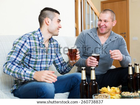 Happy men drink beer at home on a day off.Focus on the right man - stock photo
