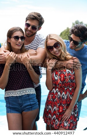 Happy men embracing women near pool on a sunny day - stock photo