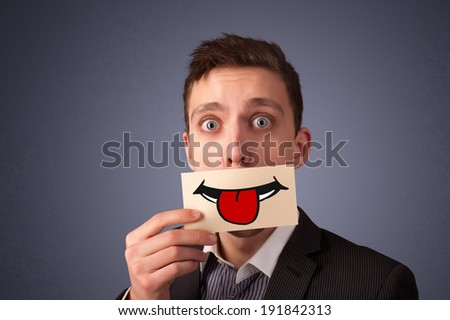 Happy men holding card with funny smiley on gradient background - stock photo