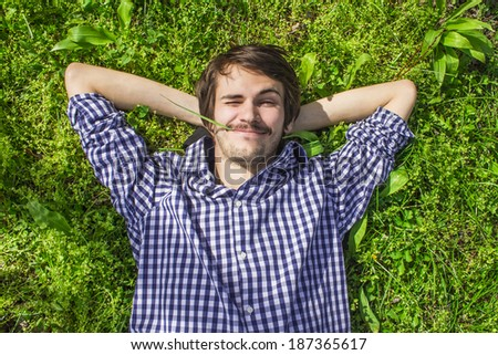 Happy men lying on the grass - stock photo