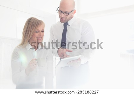 Happy mid adult business couple using tablet PC at home - stock photo